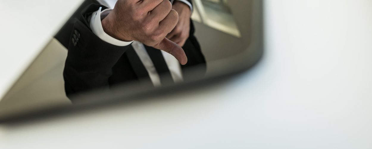 Reflection of a businessman with thumbs up in a tablet PC on the white surface of a table.